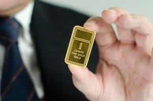 Bullion gold bar in a hand