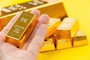 A hand with a gold bar with gold bars of various sizes in the background