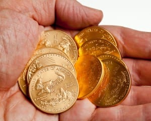 Bullion and Proof Gold American Eagle coins on a man's hand